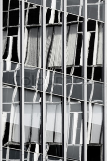 a photo of a wall of an offise building with a number windows and reflections of a near building in it