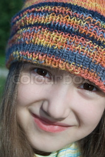 cute smiling girl in colored knitted hat