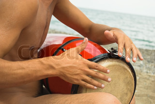 nude man playing darbuka on the beach