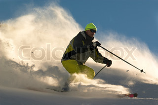 man on ski tear at full speed in cluods of snow powder