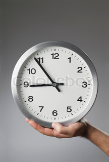 Man holding a clock in his hand.