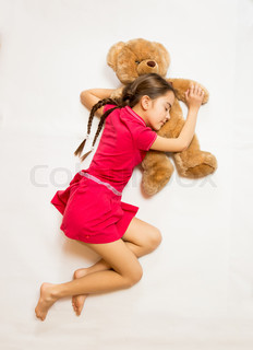 View  from top of girl lying on floor and sleeping on teddy bear