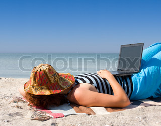 Girl with laptop computer sleep at sea coast