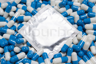 close up of condom and blue pills