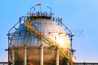 natural petrochemical gas storage tank in heavy petroleum industry estate against clear blue sky background