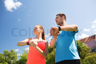 smiling people with heart rate watches outdoors