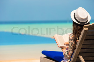Young woman read book near swimming pool