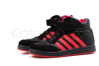 Footwear for playing sports of black colour with red strips on a thick sole.