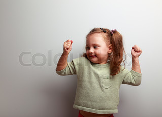 Happy smiling kid girl showing muscular and looking fun