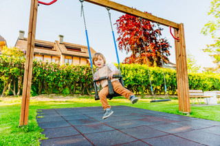 Cute toddler boy having fun on a swing on a nice summer day