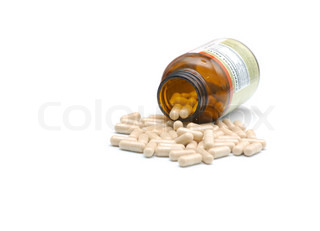 closeup of medical bottle and heap of pills fallen out from