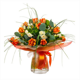 Bouquet of narcissus, tulips and other flowers in glass vase.