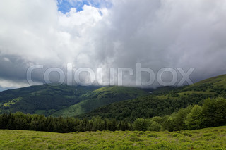 Mountain top with green meadows in the rain clouds.