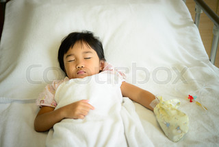 Kid sick in the hospital sleeping on bed