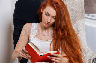 Young Woman Sitting on Chair While Reading a Book