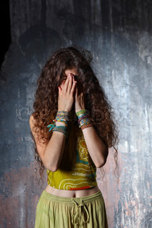 Young woman crying on a grey wall background