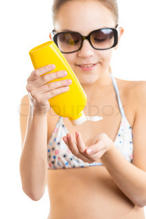 isolated portrait of cute girl applying sunscreen