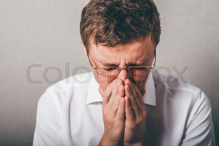 the guy blows his nose and sneezing