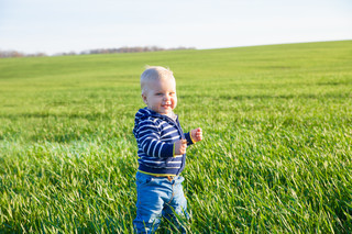 Beautiful baby boy standing in the green grass