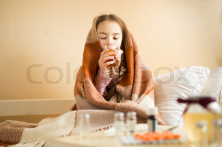 Portrait of sick girl covered in blanket drinking hot tea