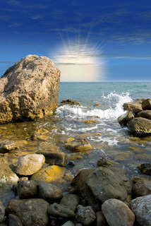Sunrise at sea coast with picturesque stones in the foreground