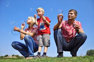Happy family blowing soap bubbles