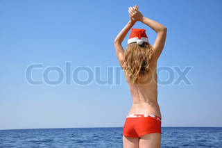 Woman wears a hat of Santa Claus on the beach