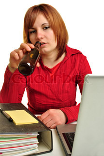 a young woman drinking at her office desk