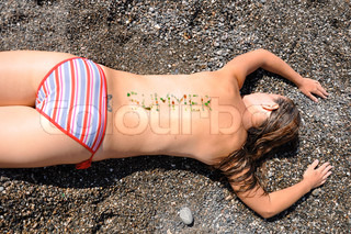 girl lying on the beach with an inscription on the back of SUMMER
