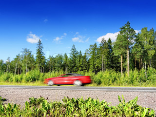 red cabrio car speeding on summer country highway, blured in motion