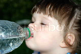 The girl drinking water from a plastic bottle