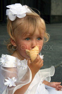 The little girl in a white dress and with a bow on a head eats ice-cream