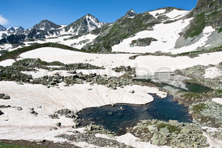 Mountain landscape with crystal river, mountain peaks, snow and sky.