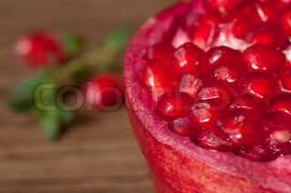 Pomegranate close-up on a brown wooden table.