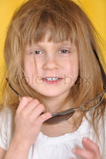Naughty little girl with a pair of broken sunglasses. Yellow background.