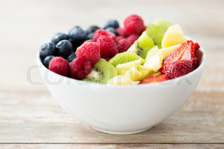 close up of fruits and berries in bowl on table