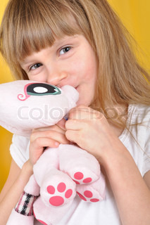 Child with a toy plush cat over the yellow background