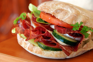 big appetizing sandwich with red ham meat, cucumber and tomatoes
