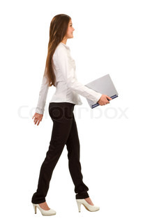 a young businesswoman walking and holding a laptop,