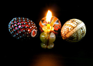 Easter eggs with candle against black background