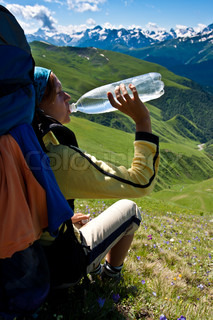 Hiker girl drinking water after hard rush and relaxing on the meadow, with mountains background.