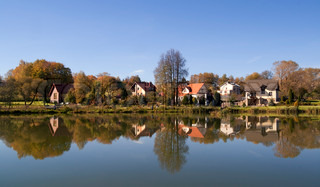 Village on river bank, reflections in water and  solar autumn day