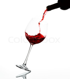 pouring red wine into wine glass on reflective surface