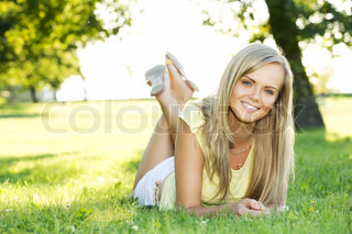 portrait of young smiling woman in the summer park