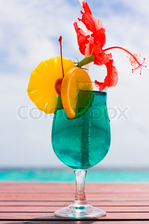 Cocktail on a beach table with a tropical fruit