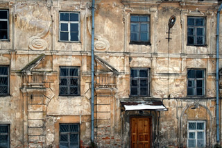 Wall of an old decrepit dilapidated building. Repair is unprofitable, the structure gradually collapses.
