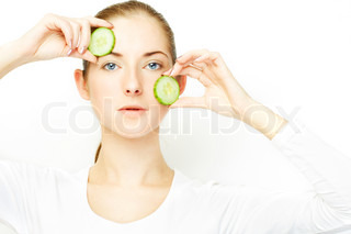 young woman, with two slices of cucumber over her face, clear skin concept theme