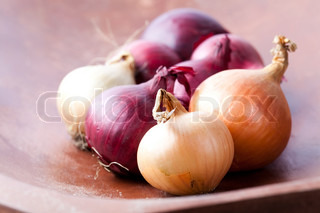 Close-up of red and yellow onions on a wooden background