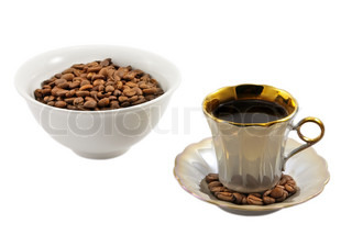 Cup of coffee and bowl with coffee beans on the white