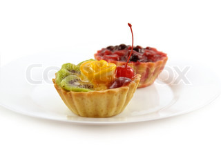 Two cupcakes with fruits and jelly on white